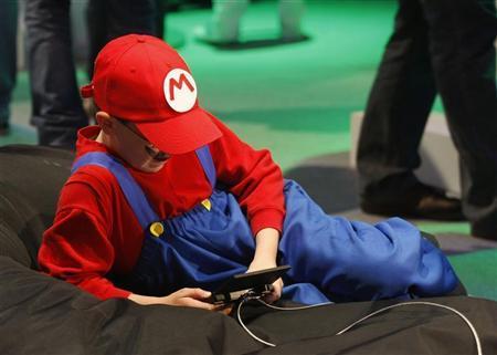 فتي يمسك بجهاز لالعاب الفيديو في معرض في كولون يوم 19 اغسطس اب 2010.