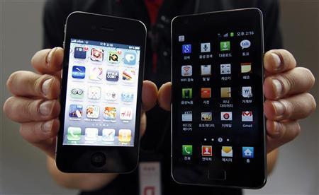 موظف شركة يعرض جهازي ابل اي فون (إلى اليسار) وسامسونج جالاكسي في سول